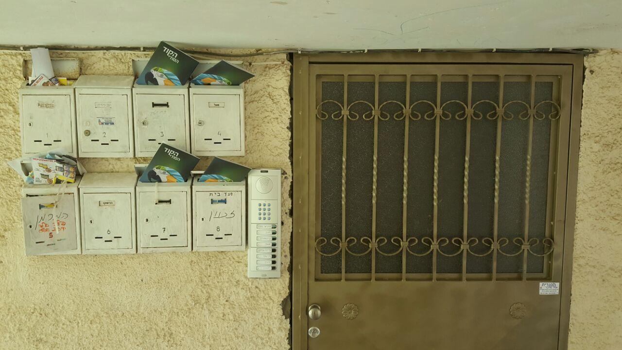 """חוברות """"הקוד הסודי"""" בתיבות דואר בקרית אליעזר (צילום: שני מועלם)"""