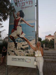 """איתנה אלקיים ושלט הפרסומת של התערוכה הכולל את תמונה משנת 1968 (צילום: יח""""צ מוזיאוני חיפה)"""