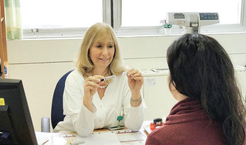 אורית ויזינגר מדריכה מטופלת בהזרקת אינסולין (צילום: דוברות שירותי בריאות כללית)