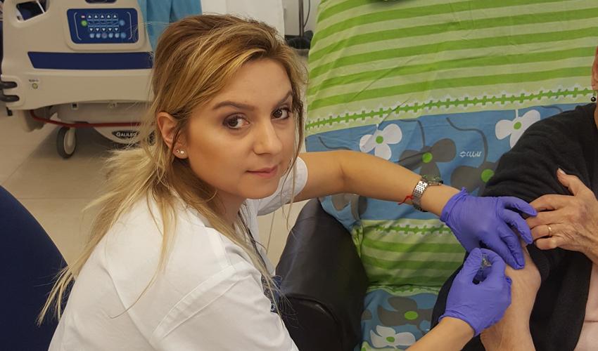 האחות רגינה דרליוק מחסנת מטופל (צילום: דוברות שירותי בריאות כללית)