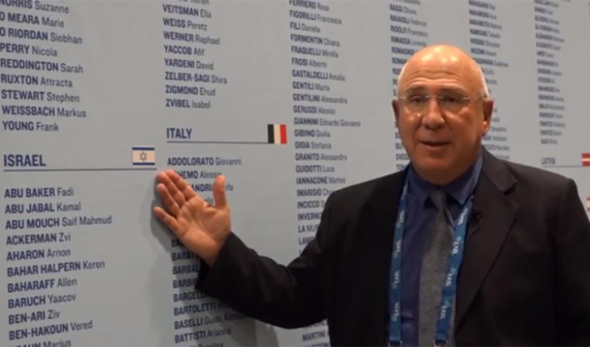 """פרופ' אלי צוקרמן ודגל ישראל בכנס בפריז (צילום: באדיבות אתר """"דוקטורס אונלי"""")"""