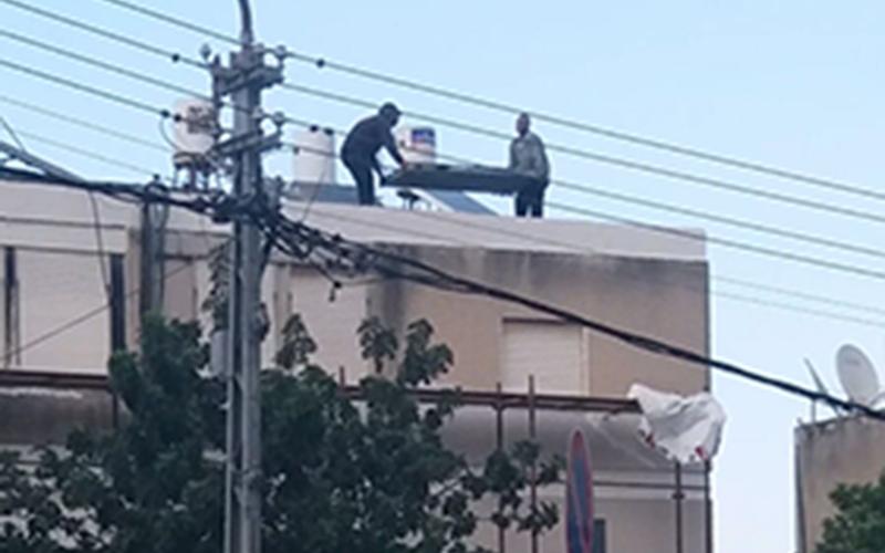 הפועלים משליכים פסולת מהגג