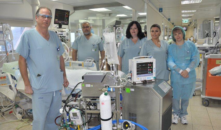 """ד""""ר אריק עדן (משמאל) וצוות היחידה לטיפול נמרץ עם מכשיר האקמו (צילום: אלי דדון)"""