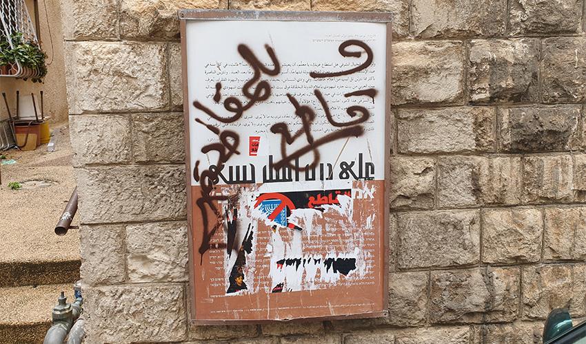 """גרפיטי על שלט הנצחה לאמיל חביבי בקריאה להחרים את הבחירות לכנסת. רג'א זעאתרה: """"זו לא מחאה פוליטית, זה ונדליזם"""""""