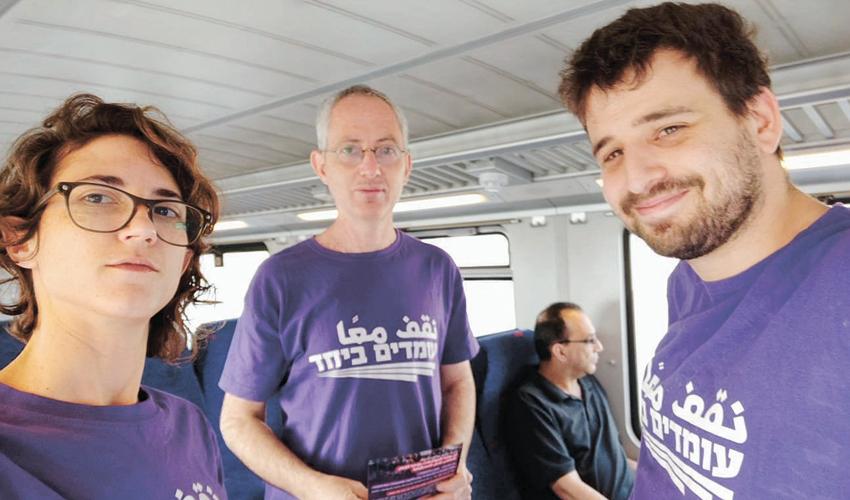 פעילים מתנועת עומדים ביחד בפעילות הסברה ברכבת (צילום: אסף יקיר)