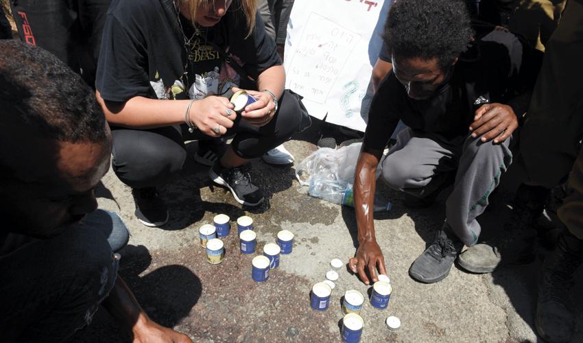 מפגינים מדליקים נרות נשמה לזכרו של סלומון טקה (צילום: רמי שלוש)