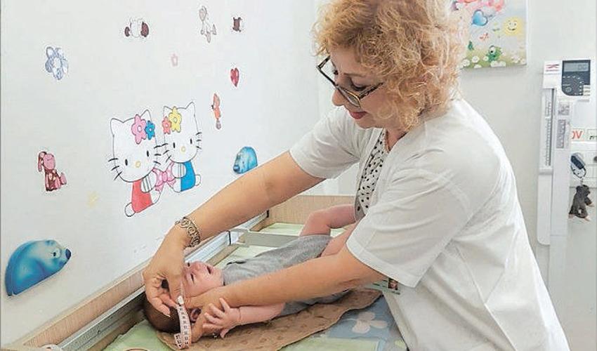 אחות טיפת חלב מודדת היקף ראש של תינוק (צילום: דוברות שירותי בריאות כללית)