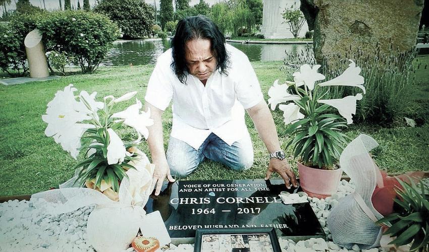 """אבי משיח על קברו של כריס קורנל. """"עיבדנו את האבל שלנו לתוך הפרויקט"""" (צילום: אלעד משיח)"""