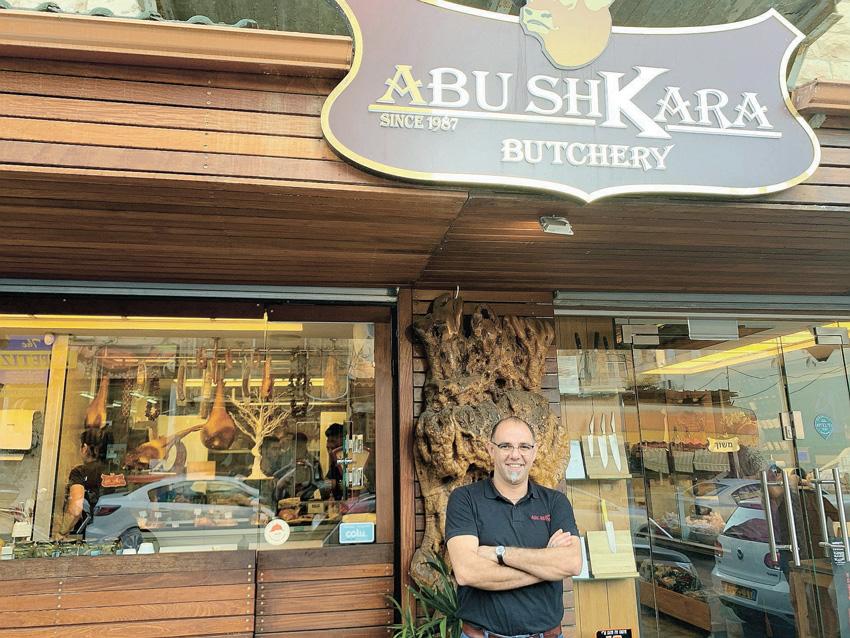 """מרואן אבו שקארה בפתח האטליז והמעדנייה. """"אני לא מזדהה עם אף אחד מלבד עם הלוגו של אבו שקארה"""" (צילום: חגית הורנשטיין)"""