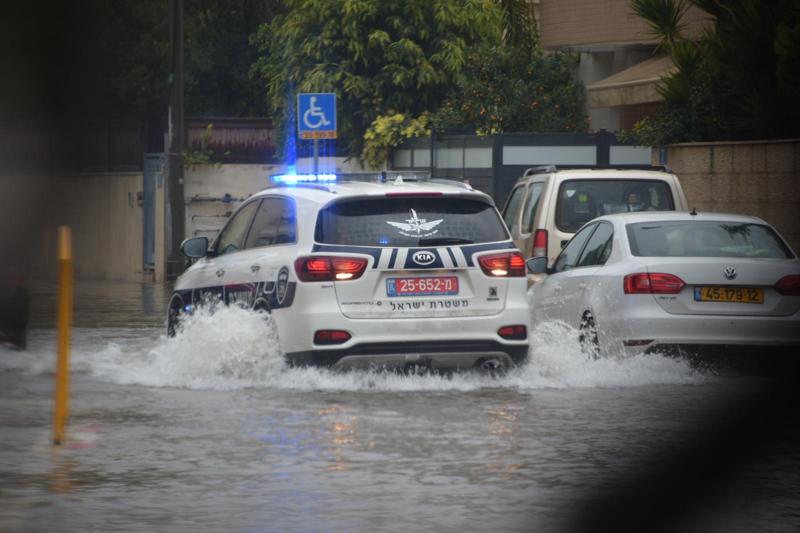 רכב משטרה בתוך שלולית ענק (צילום: דוברות משטרת ישראל)