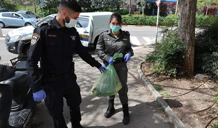 """שוטר ומג""""בניקית מחלקים חבילות מזון לקשישים בנוה יוסף (צילום: דוברות משטרת ישראל)"""