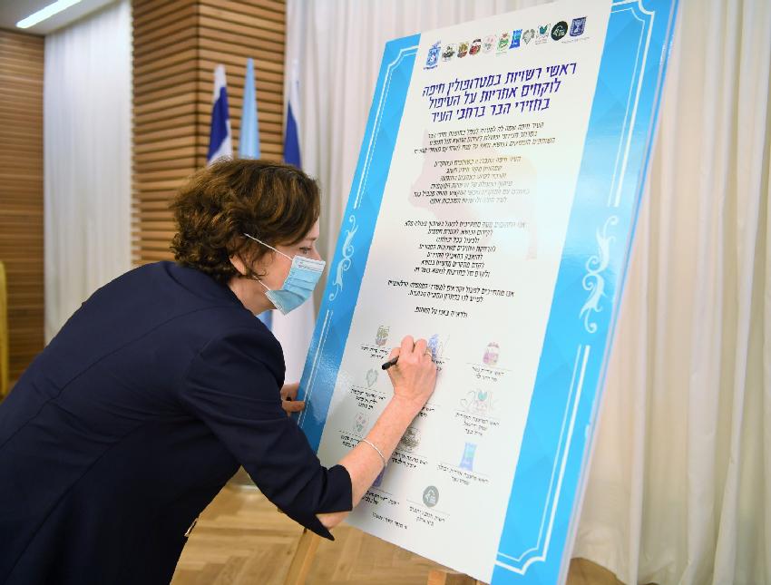 עינת קליש רותם חותמת על האמנה (צילום: ראובן כהן, דוברות עיריית חיפה)