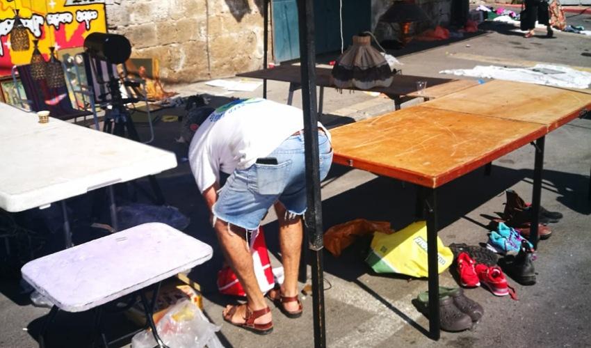 סוחר מקפל את הדוכן שלו בשוק הפשפשים (צילום: דוד מגן)