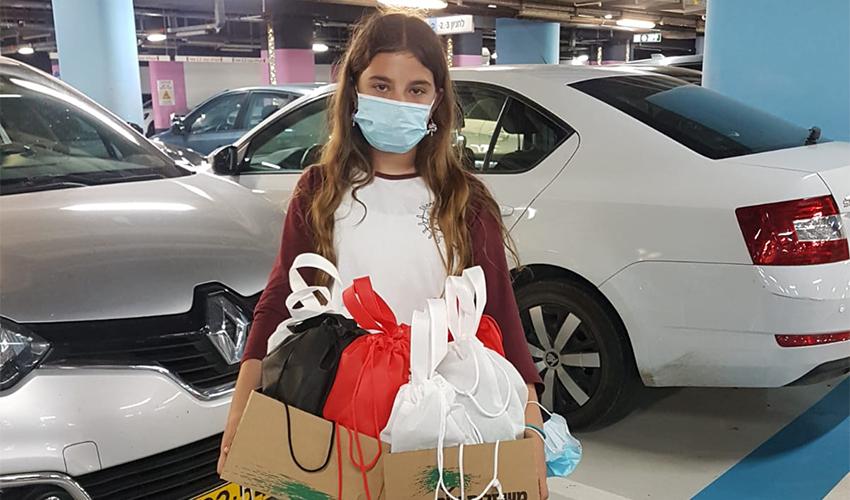 """אליה ויצמן עם חבילות השי (צילום: דוברות הקריה הרפואית רמב""""ם)"""