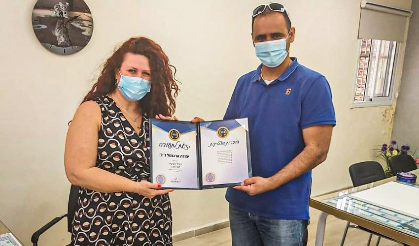 חיליק אמסלם מעניק את תעודת העובד המצטיין לאלמנה אורלי ארגנטל (צילום: דוברות עיריית חיפה)