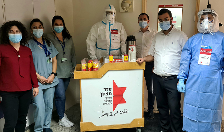 מתנדבי עמותת עזר מציון עם אנשי מחלקת הקורונה במרכז הרפואי כרמל (צילום: אלי דדון)