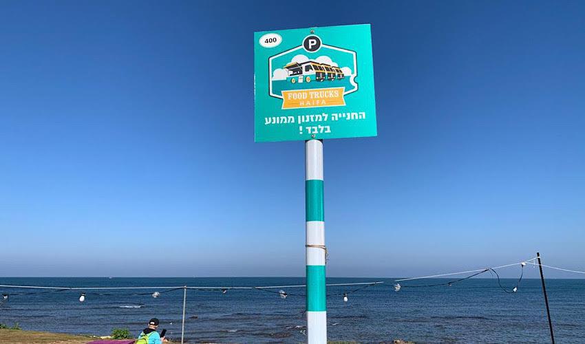 שלט של חניית פוד טראק בחוף הים (צילום: חגית הורנשטיין)