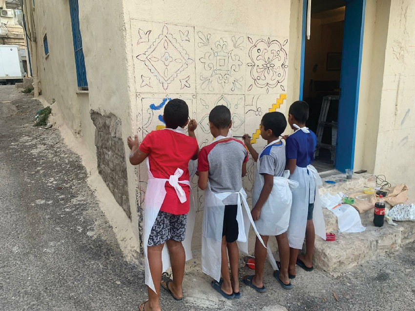 """ילדי השכונה מציירים על הקירות. """"הם כל הזמן באים ורוצים לצייר, וזה עושה לי כיף"""" (מתוך עמוד הפייסבוק קיבוץ גלויות-91)"""