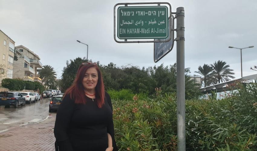 פדואה סרוג'י ליד שלט ההכוונה לשכונה שבו מופיע השם ואדי אל-ג'מאל (צילום בועז כהן)